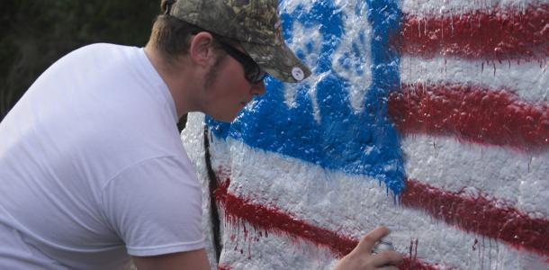 Senior Frank Daniel (left) paints the rock off Highway Nine with an American flag in remembrance of senior Ryan Seek.